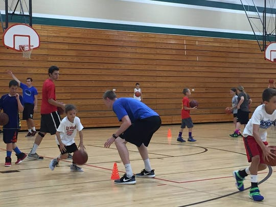 Paul Jesperson (back to camera) in a defensive stance during a drill at his basketball camp in Menomonie last week.