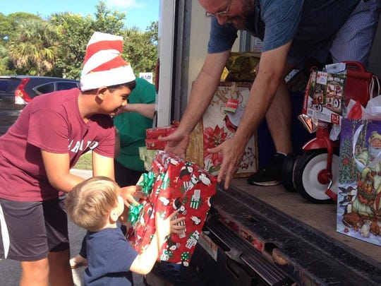 Santa's helper, Mike Kaiser (right), collects donated toys from Sun Grove Montessori School for the Making Christmas Bright program.