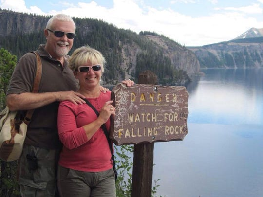 Alison Miller and Chuck Dearing stand by a scenic spot along their journey across the country.