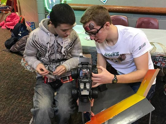 Jacob Honer helps guest John put together a remote control car.