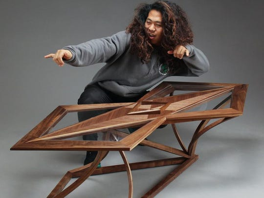 Gonzo Macabeo, showing his surf style, posing with a table of his own design.