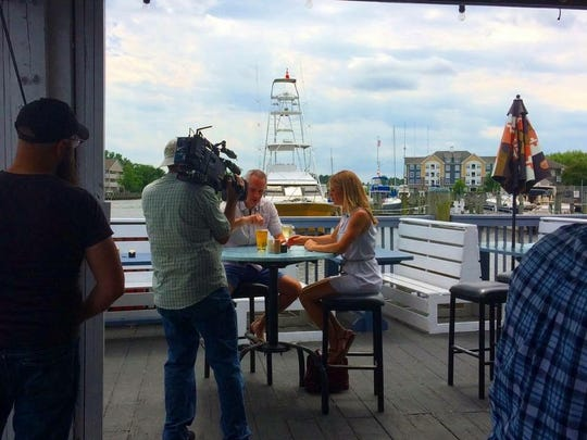 "J.D. and Jenny Schroen (left to right, center) are filmed outside of Brew River Restaurant for their upcoming episode of ""House Hunters."""
