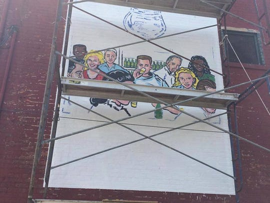 This mural is being painted on the side of Herb & Thelma's,