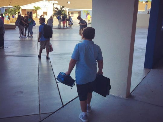 Sixth-grader Zachary Batten heads off to middle school on Wednesday, Aug. 16, 2017, the first day of classes for Collier County public school students.