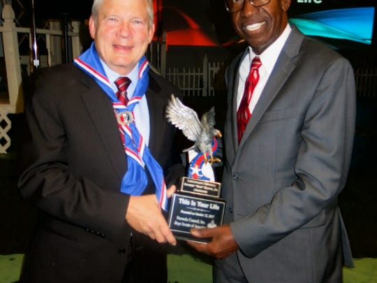 "Bob Elder receives flying trophy from fellow Eagle Scout Roy Griggs at ""This is Your Life"" celebration."