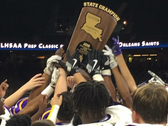 The Logansport team holds up their 2016 LHSAA Class 1A state championship trophy.