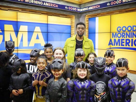 Tiana Sirmans, back row, poses for a picture with Black Panther star Chadwick Boseman. His hand rests on her shoulder.