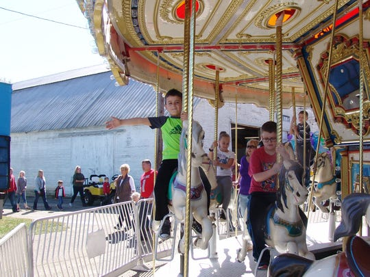 Bodie Mercer waves as he rides the merry-go-round at the Coshocton County Fair.