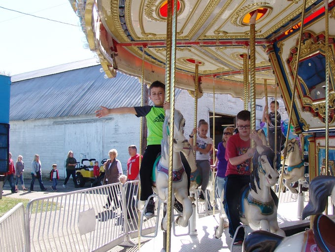Bodie Mercer waves as he rides the merry-go-round at