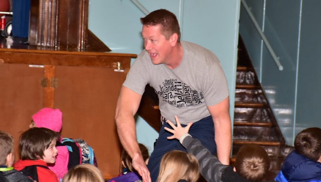 Corryton Elementary principal Aaron Maddox races through the crowd of students and high-fives each during an assembly. Corryton responded to a lip-sync challenge from Halls Middle School.