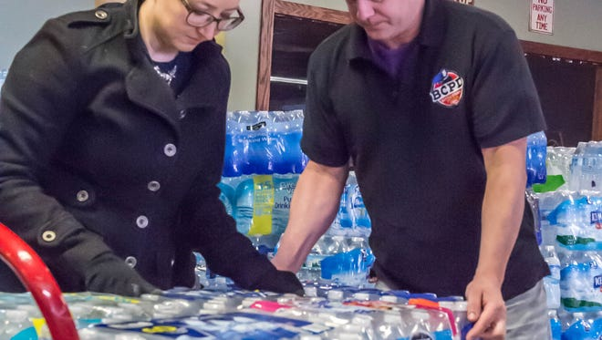 Jen Ozolins of FireKeeper Casino and B.C.P.D. co-owner of B.C.P.D. Pizza load water at  on Tuesday.