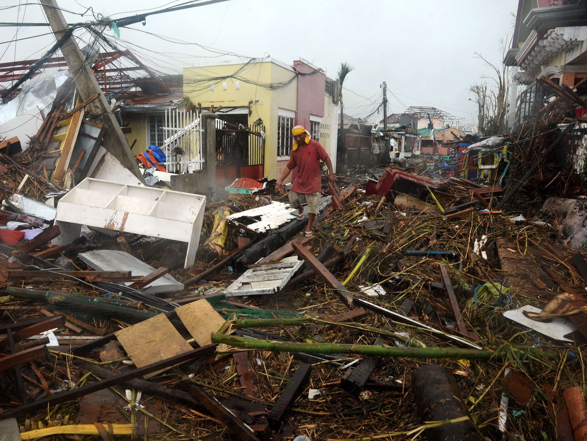 A man walks among debris of destroyed houses in Tacloban.