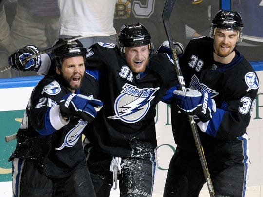 Tampa Bay Lightning's Martin St. Louis (26) celebrates his second goal with teammates Steven Stamkos (91) and Mike Lundin (39) during the third period in Game 6 of an NHL hockey Stanley Cup playoffs against the Boston Bruins in the Eastern Conference final series in Tampa, Fla., Wednesday, May 25, 2011. Tampa Bay won 5-4. (AP Photo/Phelan M. Ebenhack)