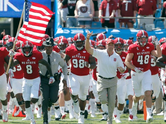 FILE - In this Sept. 2, 2017, file photo, North Carolina State head coach Dave Doeren, second from right, leads his team onto the field for an NCAA college football game against South Carolina in Charlotte, N.C. The ACC seems to be a league with one dominant team in the Clemson Tigers and several solid squads still learning how to contend on the national stage. The Wolfpack is off to their best start since Philip Rivers was the quarterback 15 years ago. (AP Photo/Bob Leverone, File)