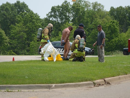 Battle Creek firefighters and police removed the clothing of a robbery suspect after he threatened bank employees by saying he had antrax.