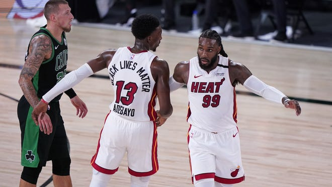Boston Celtics center Daniel Theis, left, stands by as Miami Heat's Bam Adebayo (13) and Jae Crowder (99) celebrate their 106-101 win in an NBA conference final playoff basketball game, Thursday, Sept. 17, 2020, in Lake Buena Vista, Fla.