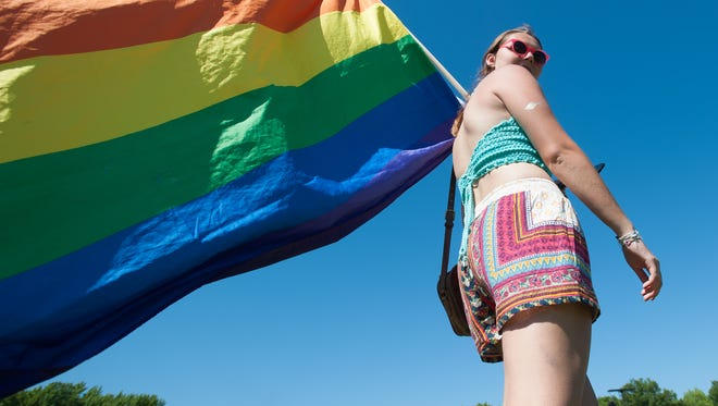 Maddie Vandermark of Belmar, N.J., carries a rainbow flag at the Firefly Music Festival in Dover.