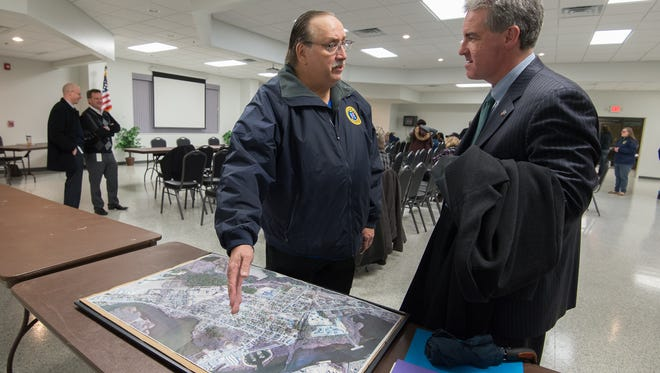 David Ruff, left, mayor of the town of Blades, talks with Shawn Garvin, secretary of DNREC, next to a map of Blades.  Recent tests have shown that PFC contamination was found in public drinking wells in Blades.