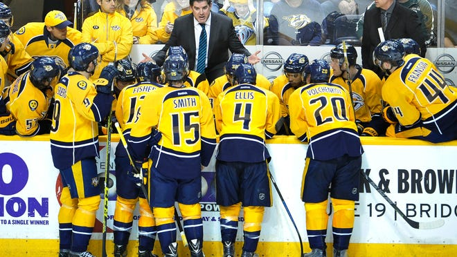 Predators coach Peter Laviolette talks with his team during a timeout against the Flames at Bridgestone Arena on Sunday.