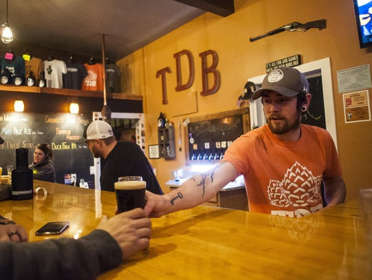 Michael Garrity, brewmaster, serves beer to a customer