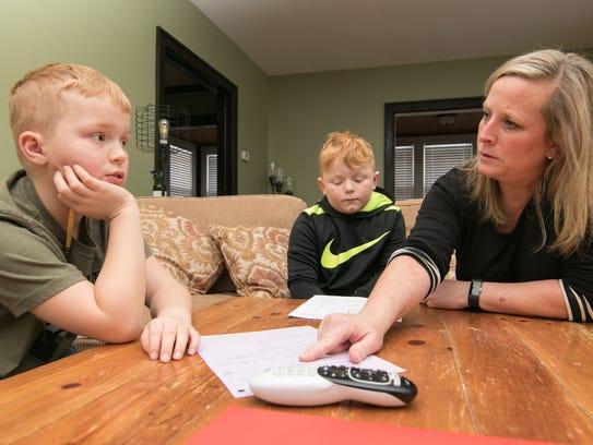 Caleb Harbin, 9, at left, asks mom Patti Dunbar for