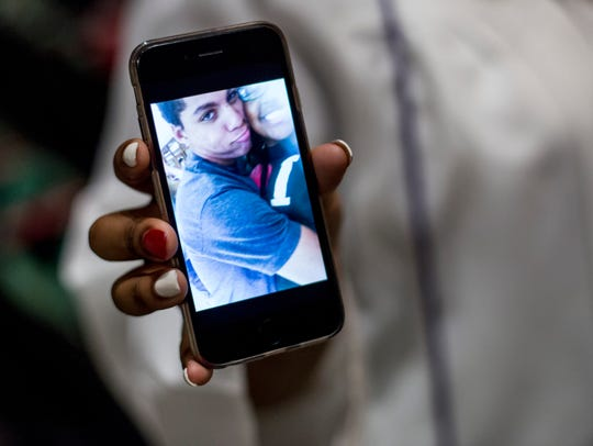 Samyra Lee, 17, shows a photograph of her friend John