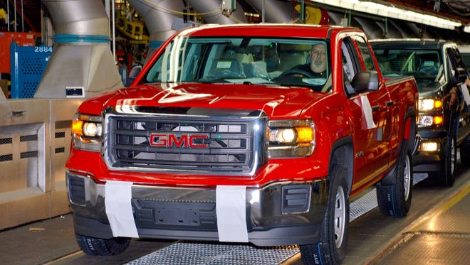 A 2014 GMC Sierra extended-cab pickup is driven off the final assembly line at Fort Wayne, Ind.