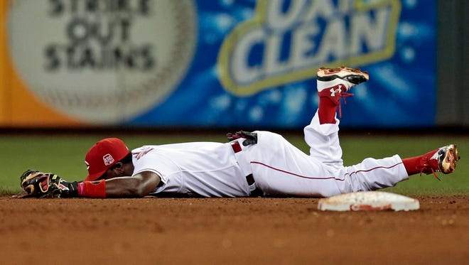 Cincinnati Reds second baseman Brandon Phillips (4) takes a moment on the ground after his diving catch for the third out in the top of the eighth inning of the MLB game between the Cincinnati Reds and the Los Angeles Dodgers at Great American Ball Park in Cincinnati on Wednesday, Aug. 26, 2015. The Reds fell to the Dodgers 7-4.