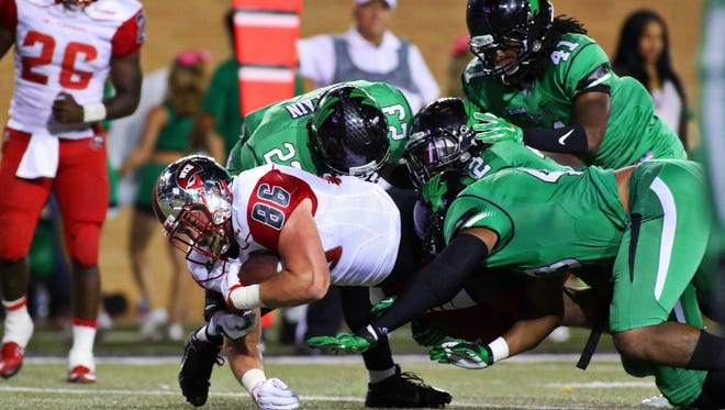 Oct 15, 2015; Denton, TX, USA; Western Kentucky Hilltoppers tight end Tim Gorski (86) is tackled by a host of North Texas Mean Green defenders during the second half of game at Apogee Stadium. Western Kentucky won 55-28. Mandatory Credit: Ray Carlin-USA TODAY Sports