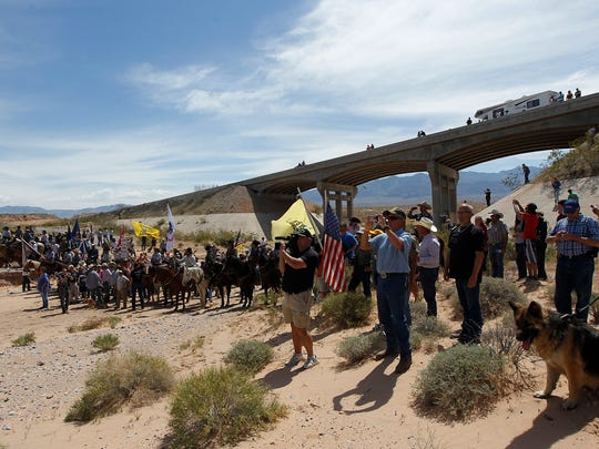 In this April 12, 2014, file photo, the Bundy family and their supporters gather together under a Interstate 15 highway overpass just outside of Bunkerville, Nevada, to confront Bureau of Land Management agents and demand the release of their impounded cattle.