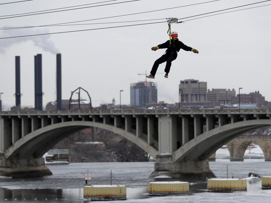 A visitor rides a zip line over the Mississippi River