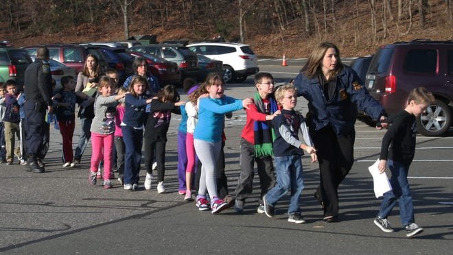 Connecticut State Police lead a line of children from the Sandy Hook Elementary School in Newtown, Conn., on Dec. 14, 2012.