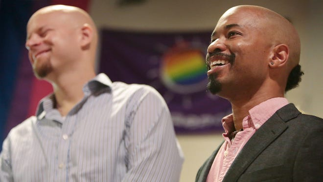 Johannes Wallmann, left, reacts to a joke told by his husband, Keith Borden, right, while speaking during Wisconsin Unites for Marriage's Marriage Bus Tour stop at the South Central LGBT Community Center in Madison, Wis., Monday, Aug. 25, 2014. The two are plaintiffs in Wolf v. Walker, challenging Wisconsin's ban on same-sex marriage. The bus continues on to Milwaukee, Racine and then Chicago Monday afternoon for a rally at Federal Plaza. On Tuesday, the 7th Circuit Court of Appeals in Chicago will hear arguments in challenges to Wisconsin and Indiana's same-sex marriage bans.