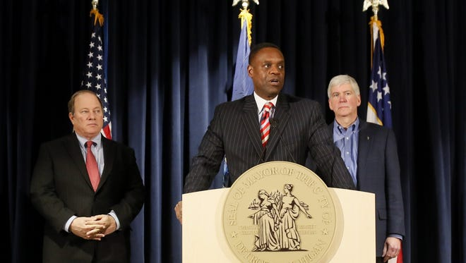 In this December 2014 photo, Detroit Mayor Mike Duggan, left, and  Michigan Governor Rick Snyder, right, listen as Detroit emergency manager Kevyn Orr addresses the media during a press conference to announce the City of Detroit's exit from bankruptcy.
