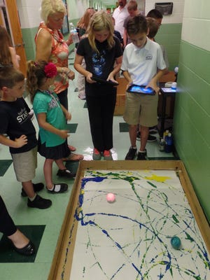 During a recent STREAM Family Night at St. Andrew Catholic School, students create a Jackson Pollock-inspired work of art with the help of iPads and Sphero balls, which are robotic balls controlled with technology. The purpose of the STREAM event was to showcase learning through the subjects of Science, Technology, Religion, Engineering, Art and Math.