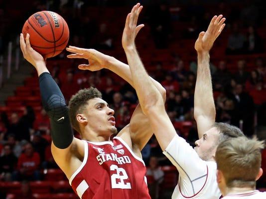 Stanford forward Reid Travis (22) shoots as Utah forward David Collette, left, defends during the first half during an NCAA college basketball game Thursday, Feb. 8, 2018, in Salt Lake City. (AP Photo/Rick Bowmer)