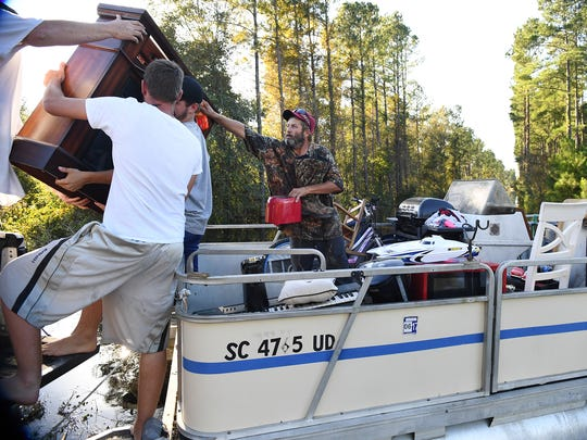 Jason Larrimore, far left, John Boothroyd, Holden Burroughs and George Grainger, right, load items recovered from their families' Brittons Neck homes from a boat to a truck since Hurricane Matthew caused flooding in the Pee Dee region. Thursday, October 13, 2016.