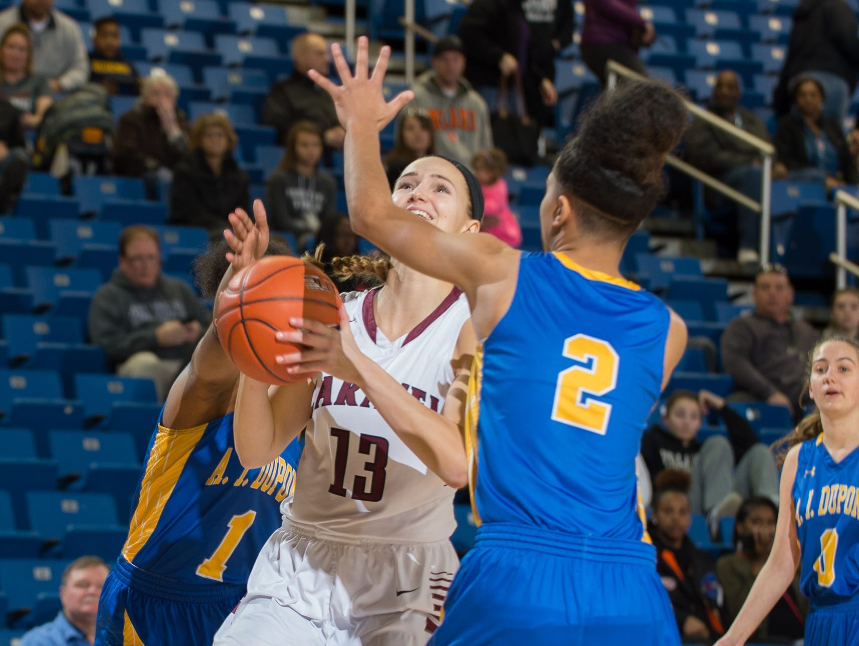 Caravel's Grace Lange (13) drives through A.I. duPont's defense for a shot in the quarterfinals of DIAA Girls Basketball Tournament at the University of Delaware.