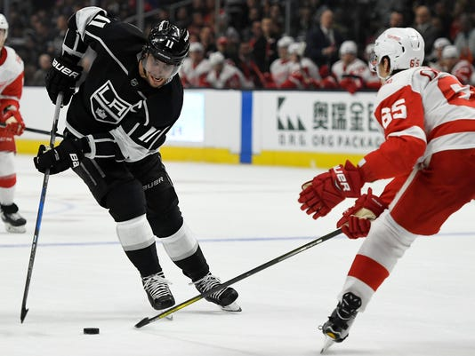 Los Angeles Kings center Anze Kopitar, of Slovenia brings the puck up the ice against Detroit Red Wings defenseman Danny DeKeyser during the second period of an NHL hockey game Thursday, March 15, 2018, in Los Angeles. (AP Photo/John McCoy)