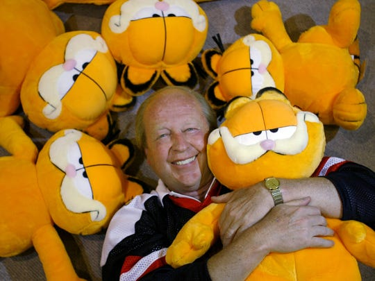 AP 2003 File photo After his cartoon ?Gnorm the Gnat? failed to create a buzz, Jim Davis returned to the drawing board and created ?Garfield.? ** ADVANCE FOR WEEKEND EDITIONS JULY 17-20 **Jim Davis hugs a stuffed version of his cartoon creation Garfield the Cat surrounded by others as he poses at his company PAWS Inc. in Albany Ind. June 26 2003. Davis is celebrating Garfield's 25th year in syndication. (AP Photo/Michael Conroy)