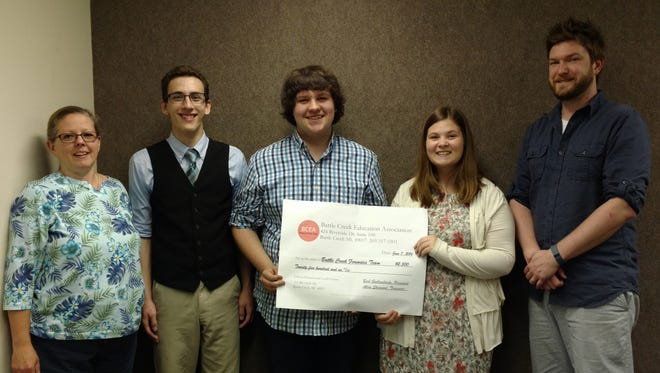 Battle Creek Education Association President Barb Giallombardo stands with Battle Creek Central High School forensics team members (left to right) Dylan Gagne, Fred Jankowski and Rachel Sidnam and their coach,  William Lapham.