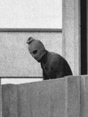 A member of the Palestinian terrorist group which seized members of the Israeli Olympic team at their quarters at the Munich Olympic Village appears with a hood over his face on the balcony of the village building where the commandos held their hostage in this Sept. 5, 1972 file photo.