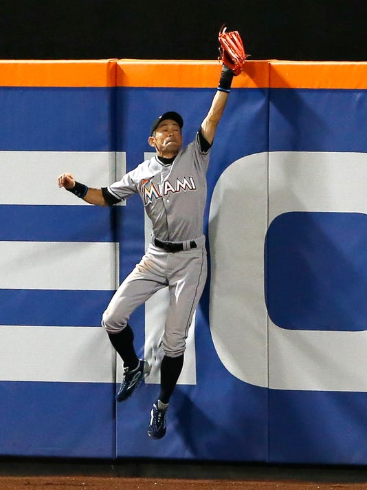 Miami Marlins right fielder Ichiro Suzuki makes a leaping catch at the wall of a ball hit by New York Mets Curtis Grandson during the fifth inning of a baseball game, Wednesday, Aug. 31, 2016, in New York. (AP Photo/Kathy Willens)