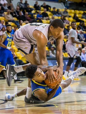 Delaware's Anthony Mosley falls to the court as he and Towson guard Mike Morsell fight for posession of the ball in second half of the University of Delaware's 83-56 loss to Towson University at the SECU Arena in Towson, Md. on Thursday night.