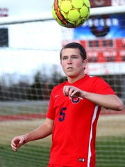 Oakland Soccer senior Noah McClard heads the ball on