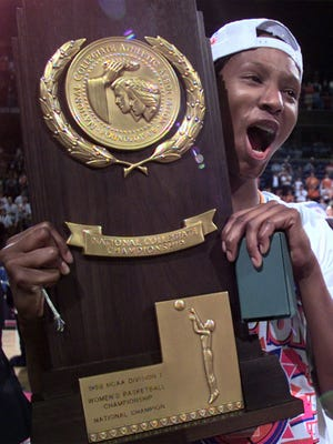 Tennessee's Chamique Holdsclaw holds the championship trophy after she and her teammates beat Louisiana Tech 93-75 in the championship game of the Women's Final Four at Kemper Arena in Kansas City, Mo., Sunday, March 29, 1998.