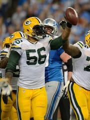 Packers linebacker Julius Peppers (56) raises the ball after recovering a fumble against the Detroit Lions on Sept. 21 at Ford Field. Will the success of the Peppers signing convince general manager Ted Thompson to delve into free agency?