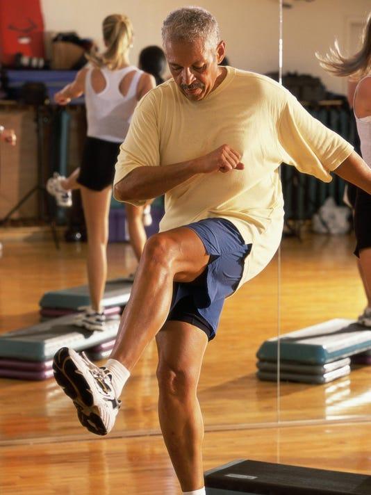 Senior man doing step aerobics in a gym