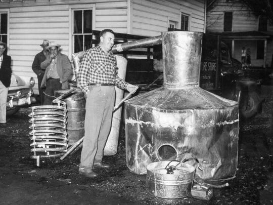 Sevier County Sheriff Ray C. Noland shows off a 500-gallon still seized in Tim McMahan's barn at Boyds Creek on Dec. 5, 1955.