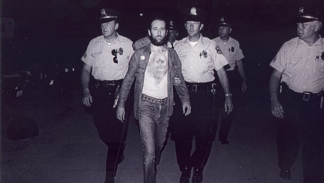 """1972: Comedian George Carlin is led away by Milwaukee police after being arrested for his performance of """"Seven Words You Can Never Say on Television."""""""